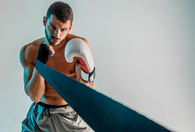 Boxer confiant avec bandage de boxe et gant sur les mains. jeune sportif européen barbu. isolé sur fond gris avec une lumière turquoise. tournage en studio. espace de copie