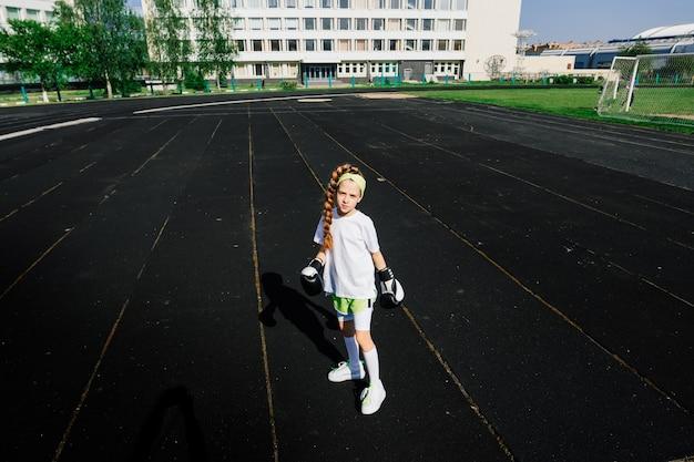 Boxer enfant féminin dans des gants, concept de féminisme. retour à l'école, cours d'entraînement physique.