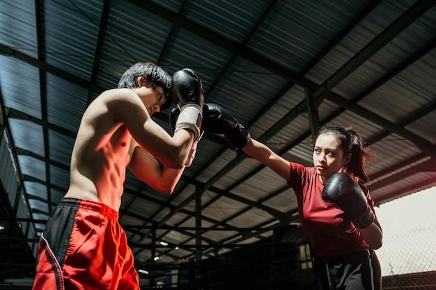 Boxer femelle avec mouvement de jab en compétition contre boxeur masculin au camp de boxe
