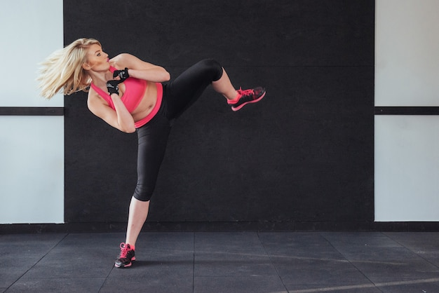 Boxer femme donnant un coup de pied dans la salle de sport sur blanc noir