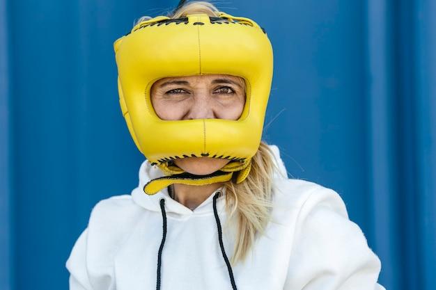 Boxer femme portant un couvre-chef jaune, regardant la caméra dans un fond bleu. femmes boxeurs, sport et concept de développement personnel.