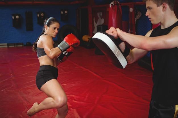 Boxer femme pratiquant avec entraîneur