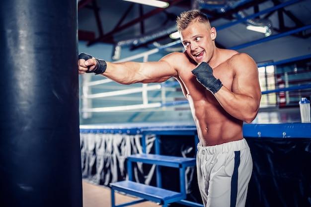 Boxer masculin formation avec sac de boxe dans la salle de sport sombre.