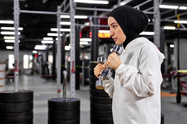 Boxer musulmane en vêtements de sport blancs hijab debout dans la pose de combattant avec des haltères, jeune femme arabe faisant des exercices, menant un mode de vie sain sport dans les pays islamiques, concepts relatifs aux droits des femmes