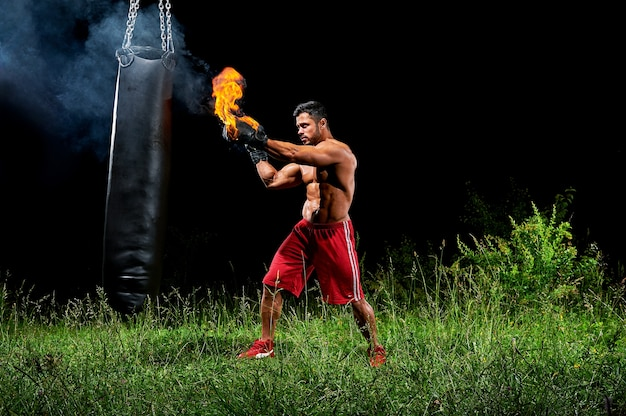 Boxer professionnel punching sandbag à l'extérieur avec son boxe glo