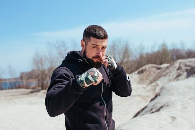 Un boxeur gonflé s'entraîne sur le sable