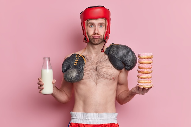 Un boxeur mâle maigre triste porte un chapeau et des bosquets de boxe autour du cou détient une pile de beignets et une bouteille de lait.
