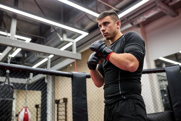Un boxeur masculin adulte confiant se tient en position, effectue des exercices en ring dans une salle de sport. l'entraînement du boxeur. concept de sport et de motivation