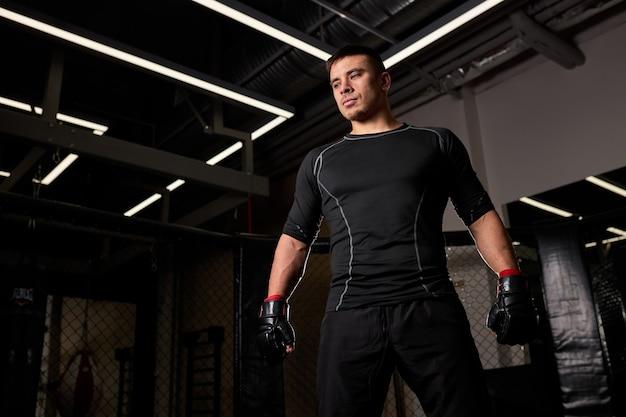 Un boxeur masculin confiant dans des gants de boxe se tient prêt à se battre sur le ring, avant ou après le combat. concept de kickboxing.