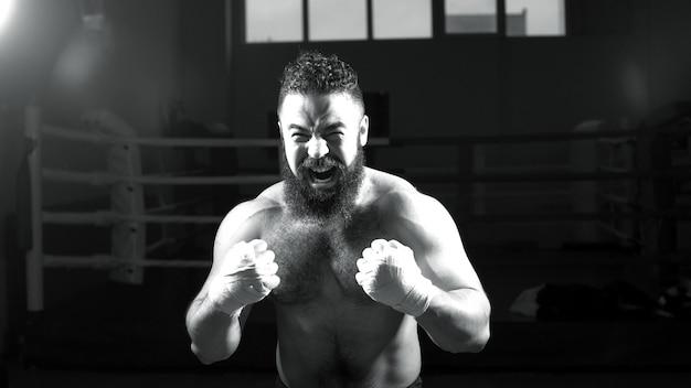 Boxeur masculin. jeune homme pratique ses mouvements de boxe. boxer homme intense jetant des coups de poing.