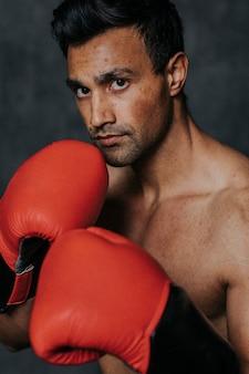 Boxeur masculin musclé avec les gants de boxe rouges