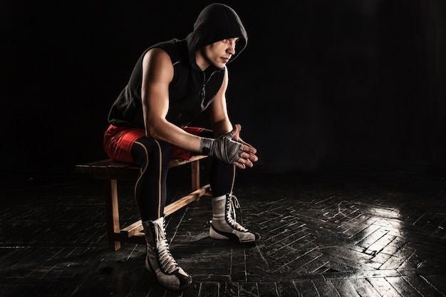 Boxeur musclé assis et reposant sur le noir