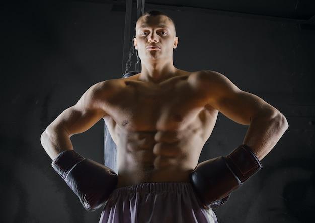 Le boxeur professionnel se tient dans la position de combat et regarde l'ennemi d'un air menaçant
