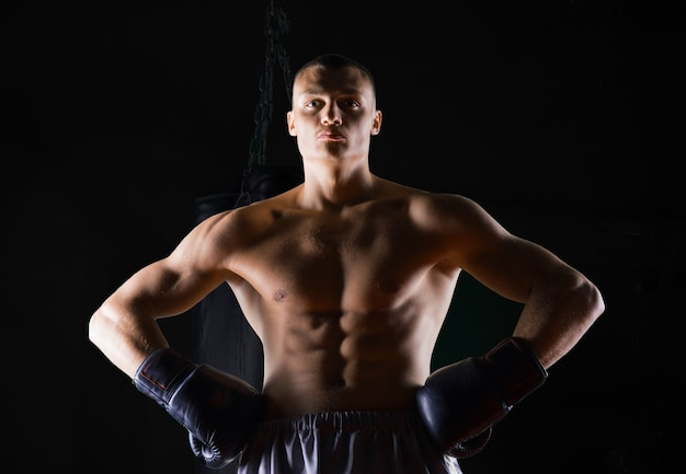 Un boxeur professionnel se tient dans la salle de sport et regarde avec confiance la caméra