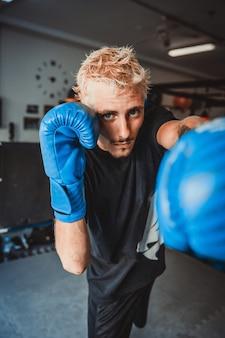Le boxeur puissant aux cheveux blonds tire un crochet du gauche.