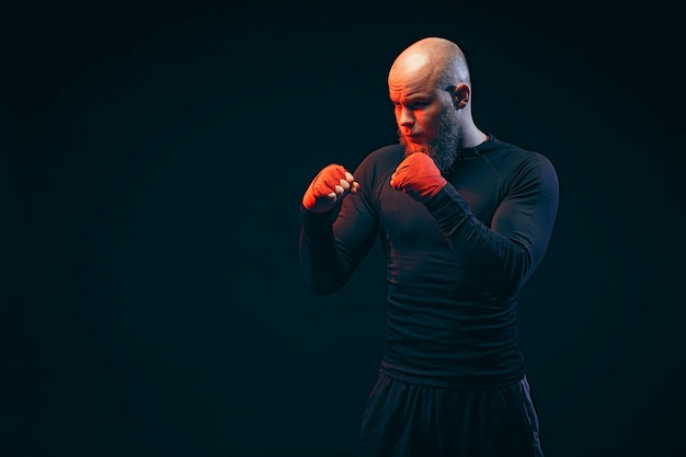 Boxeur sportif combattant sur mur noir