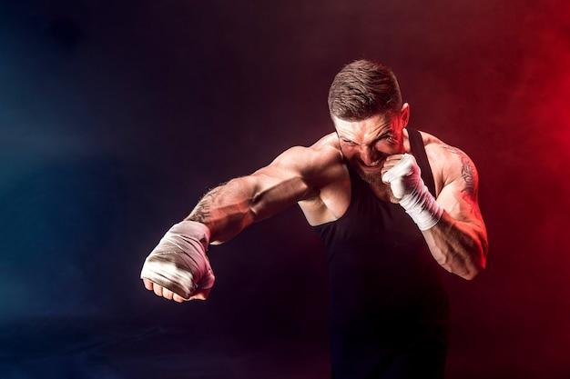 Boxeur sportif muay thai combats sur fond noir avec de la fumée.