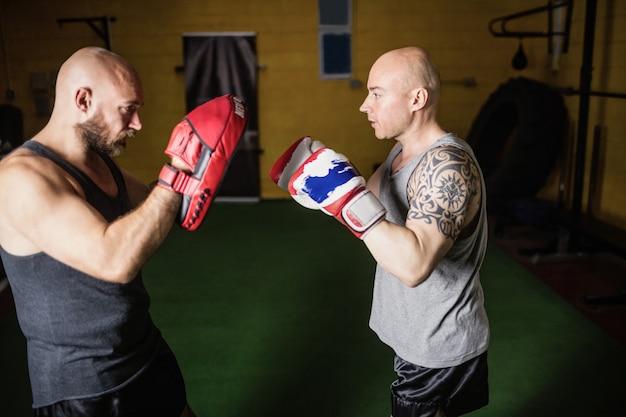 Boxeurs pratiquant la boxe dans le studio de fitness