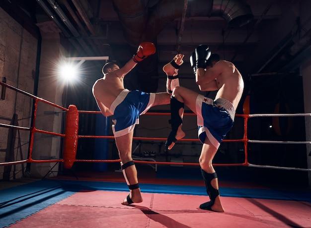 Les boxeurs s'entraînent au kickboxing sur le ring au club de santé