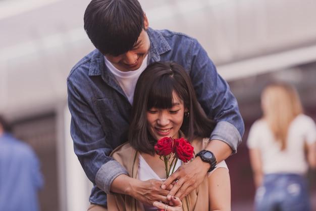 Boy étreindre derrière sa petite amie et lui donnant des roses