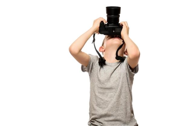Boy prend des photos sur l'appareil photo. portrait. isoler sur fond blanc.