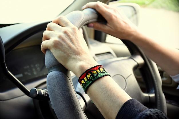 Bracelet d'amitié bricolage fait à la main avec motif drapeau rasta et symbole de paix sur le poignet des femmes