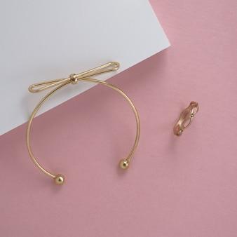 Bracelet et bague dorés modernes sur une surface blanche et rose