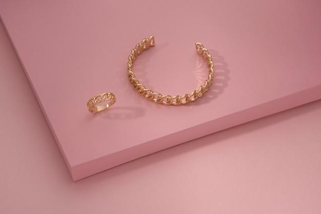 Bracelet en forme de chaîne dorée et bague sur papier rose