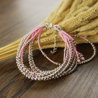 Bracelet multi-rangs rose sur table en bois