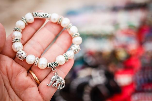 Bracelet de perles sur la main de la femme.