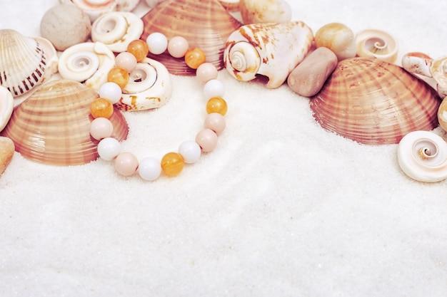 Bracelet pour femme composé de perles, coquillages, étoiles et pierres sur le sable.