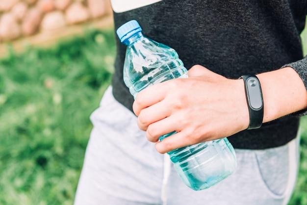 Bracelet de remise en forme à portée de main et bouteille d'eau sur fond d'herbe. mode de vie sain.