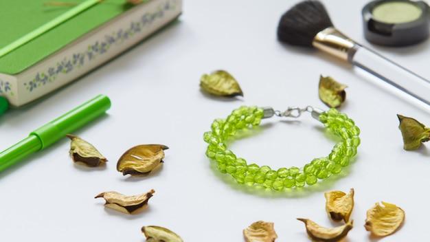 Bracelet vert et stylos sur fond blanc