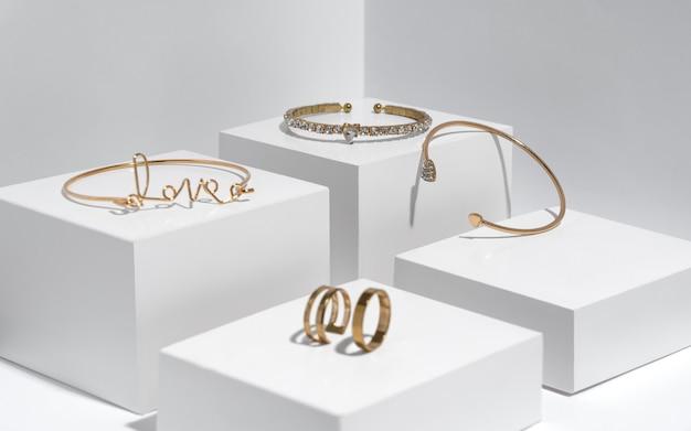 Bracelets et bagues en or sur des boîtes blanches avec espace de copie