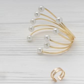 Bracelets et bagues en perles et diamants dorés sur une surface en bois blanche
