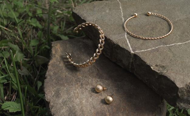 Bracelets et boucles d'oreilles en forme de chaîne en or moderne et en forme de spirale sur un rocher en plein air avec espace de copie
