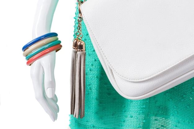 Bracelets colorés sur mannequin féminin. ensemble de bracelets lumineux pour femme. bourse blanche et bijouterie. vente d'accessoires colorés.
