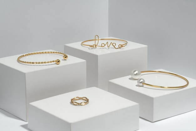 Bracelets d'or et bague sur cubes blancs eith copy space