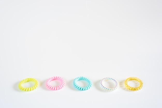 Bracelets en plastique de différentes couleurs, isolés selon un motif disposé en blanc.