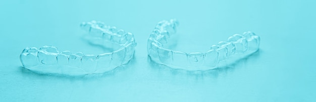 Brackets dentaires invisibles, aligneurs de dents sur fond turquoise. accolades en plastique pour dentisterie pour redresser les dents.