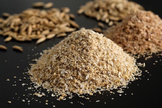 Bran d'avoine avec une mouture large, avec des grains d'avoine et de blé sur un fond noir.