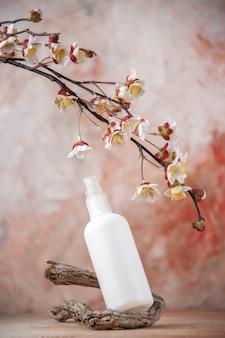 Branche d'arbre de bouteille de pulvérisation vide de vue de face et branche de fleur sur le fond nu