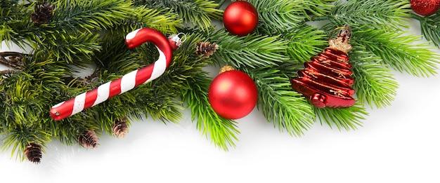 Branche d'arbre de noël aux fruits rouges et décorations sur fond blanc