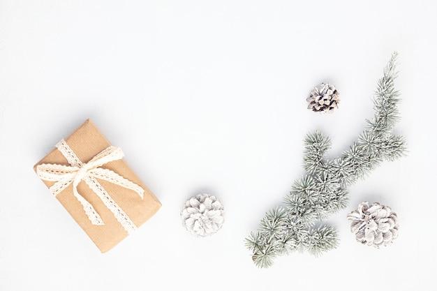 Branche d'arbre de noël et boîte-cadeau enveloppée dans du papier kraft organique, mise à plat, vue du dessus