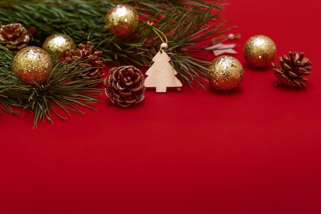 Branche d'arbre de noël décorée de boules brillantes de pommes de pin et de jouets en bois sur fond rouge