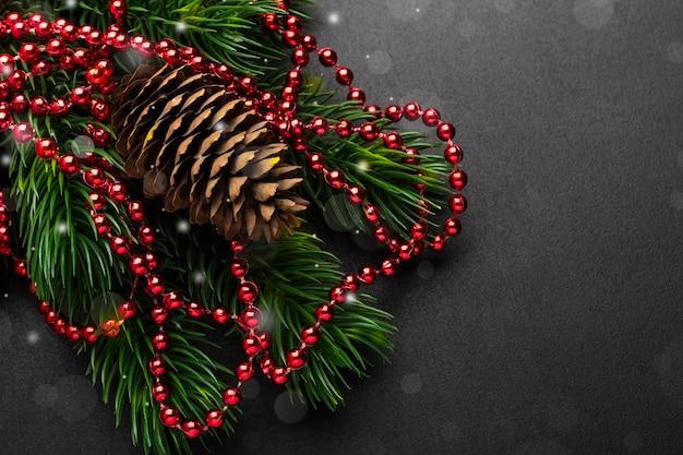 Branche d'un arbre de noël et d'une pomme de pin avec des décorations sur fond noir