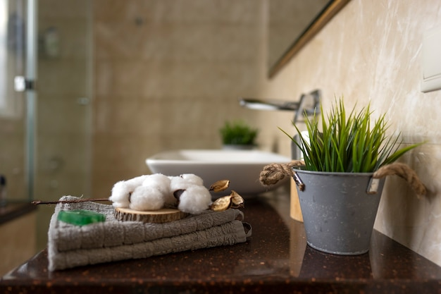 Une branche blanche de coton se trouve sur une serviette en coton dans une salle de bains moderne