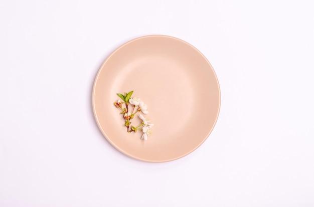 Une branche de cerises sur une plaque beige sur fond blanc. mise à plat, espace copie, 8 mars, fête des mères, bannière. vue d'en-haut