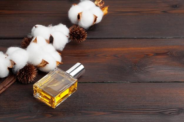 Branche de coton avec une bouteille de parfum sur fond de bois