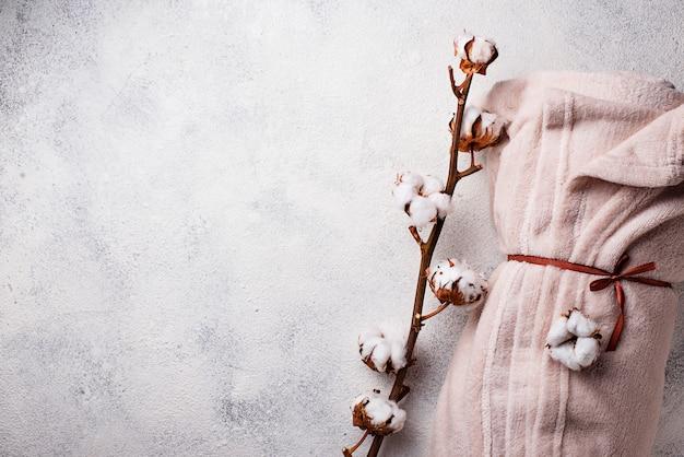 Branche de coton et couverture sur fond clair